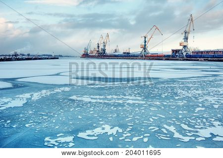 Cargo trade port on the frozen river Daugava in Riga during unloading and loading of railway cars