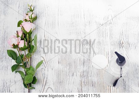 Cream for the body and hand of a wadded pad on a white wooden background isolation