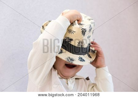 Baby Boy In Fashion Hat Covered Eyes. Child Beauty Style, Well Dressed Boy Sitting Over Gray Backgro