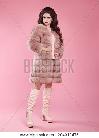 Fashion woman look. Brunette lady in fur coat and leather high boots, lady portrait over pink studio background. Fashionable beautiful brunette model in winter style.