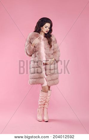 Fashion style attractive woman in fur coat and leather high boots, lady portrait over pink studio background. Fashionable beautiful brunette model in winter style.