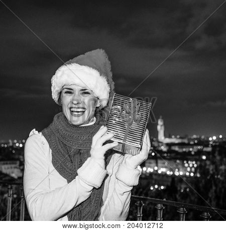 Happy Young Woman In Florence, Italy Shaking Christmas Gift