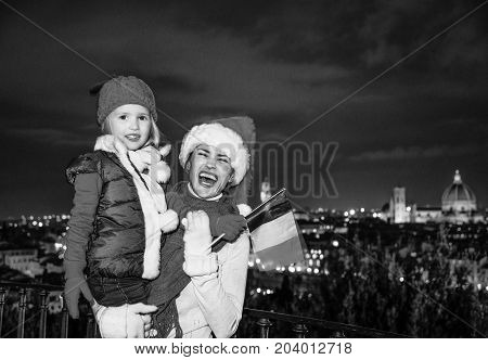Smiling Mother And Daughter In Christmas Hats With Italian Flag