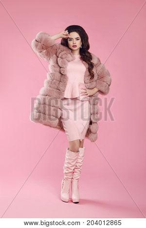 Beauty fashion elegant woman in fur coat over pink. Fashionable brunette lady wearing stylish dress and leather high boots, posing isolated on studio background. Glamour luxury style apparel.