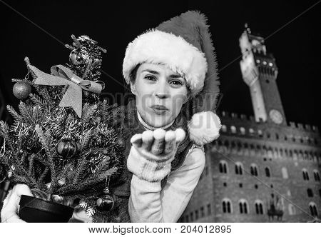 Happy Woman With Christmas Tree In Florence Blowing Air Kiss