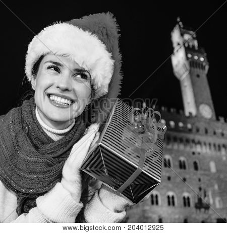 Happy Modern Woman In Florence, Italy Shaking Christmas Gift