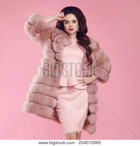 Brunette Woman in fur coat over pink. fashion studio photo of gorgeous sensual woman with long wavy hair in luxurious dress and fur coat