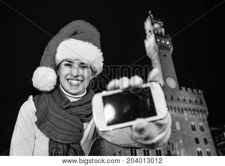 Woman In Christmas Hat Showing Smartphone's Blank Screen, Italy