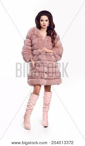 Fashion lady in pink fur coat and leather high boots, beautiful brunette model in winter style isolated on studio white background. Fashionable vogue photo.
