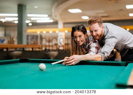 Happy couple playing snooker and billiards at club