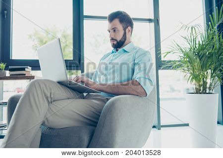 Low Angle Of Successful Focused Pedant Lawyer, Browsing Data On His Laptop, Sitting At Light Modern