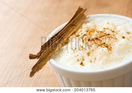 Arroz con leche. Rice pudding with cinnamon on wooden background