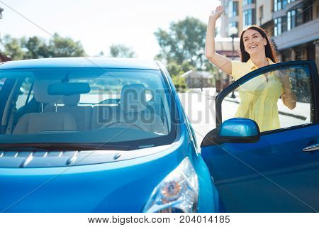 Good morning. Happy attractive cheerful woman standing near her car and smiling while waving to her friend