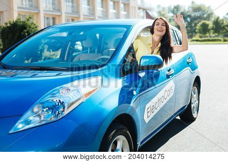 Seeing a friend. Delighted positive joyful woman driving an electro car and leaning out of the window while greeting her friend