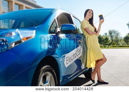 Day off work. Delighted beautiful happy woman standing near her car and resting while drinking coffee
