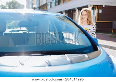 Auto owner. Nice pleasant cheerful woman holding a cup of coffee and looking at her car while opening its door