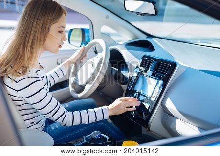 Lets go. Nice pleasant young woman holding the wheel and pressing the button while starting her car