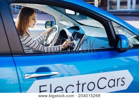 Technology in machinery. Nice attractive serious woman sitting behind the wheel and pressing a button on the sensory panel while starting her car
