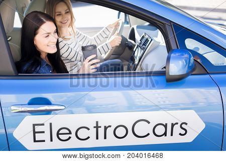 Great mood. Cheerful pleasant beautiful women sitting in the car and enjoying their ride while being in a great mood