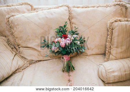 Bridal bouquet. The bride's bouquet. Beautiful bouquet of white peonies, cream roses and greenery, decorated with orange silk ribbon, lies on gray sofa