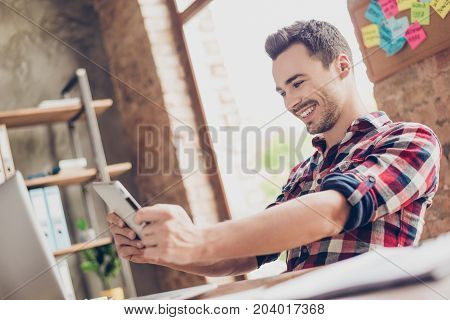 Cheerful young brunet attractive hipster worker is plying a game on his tablet in office. He is very excited wearing casual smart has a beaming smile poster