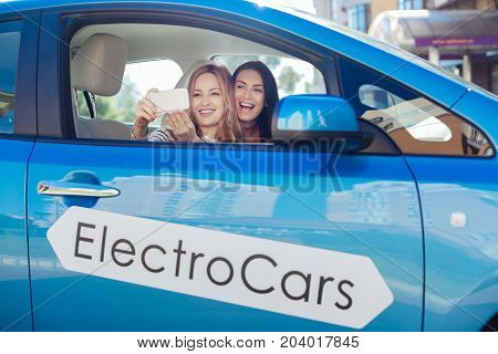 Moments to remember. Cheerful happy female friends sitting in the car together and smiling while taking photos