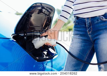 Charging station. Close up of an electro charger of a modern car being used by a nice pleasant woman for charging