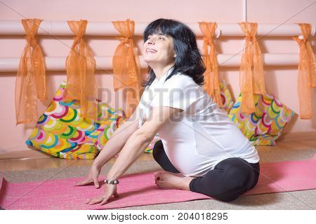 Pregnancy Yoga and Fitness concept. Healthy maternity lifestyle concept. Happy smiling 40 week pregnant middle aged caucasian woman sitting in lotus doing yoga exercises.