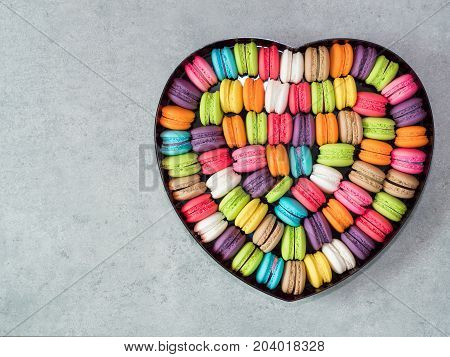 Top view of French colorful macarons in the heart shape box on bare cement background