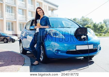 Full of vitamins. Delighted beautiful pretty woman holding orange juice and drinking it while visiting a charging station