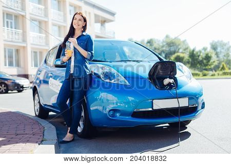 Freshly made juice. Happy delighted nice woman leaning on her electro car and smiling while enjoying her freshly made orange juice