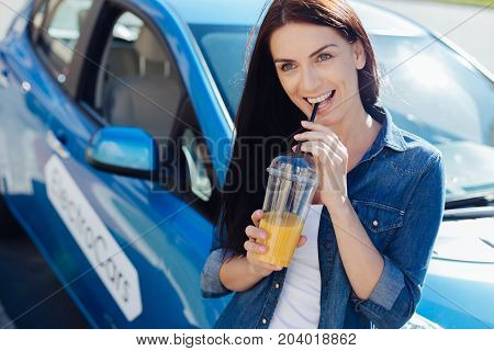 Orange juice. Positive nice good looking woman holding a straw and smiling while drinking orange juice