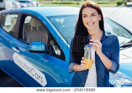 Tasty drink. Cheerful nice good looking woman standing in front of her car and smiling while holding orange juice