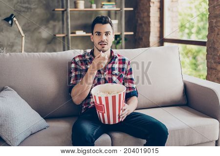 Portrait Of Impressed Brunet Attractive Hipster With Bristle In Shirt Eating Pop Corn While Watching