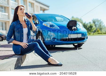 Fizzy drink. Positive brunette nice woman holding a bottle and drinking soda while sitting on front of her car