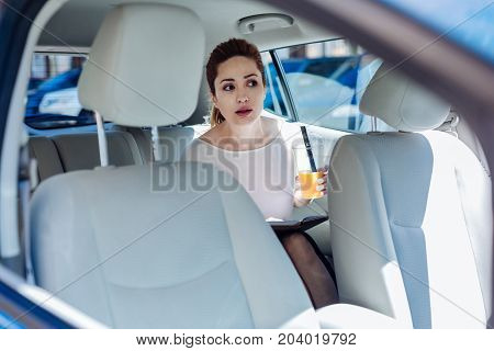 Pleasant ride. Attractive nice pleasant woman sitting on the back seat of the car and drinking orange juice while holding a notebook