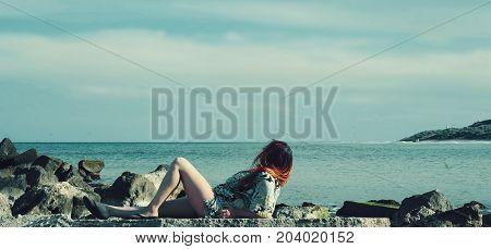 Young girl lying on rocks near the ocean admiring the ocean.