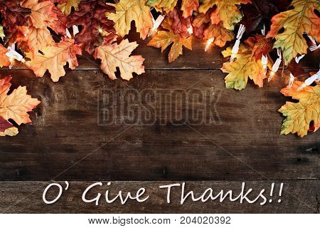 Rustic fall background of autumn leaves and decorative lights with O Give Thanks text over a rustic background of barn wood. Image shot from overhead.