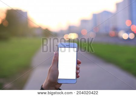 Closeup of female hand holding modern smartphone with blank screen, display at night city
