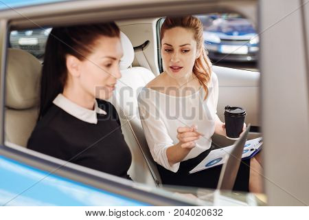 Ride in the car. Smart professional attractive businesswoman sitting together in the car and discussing work while working together