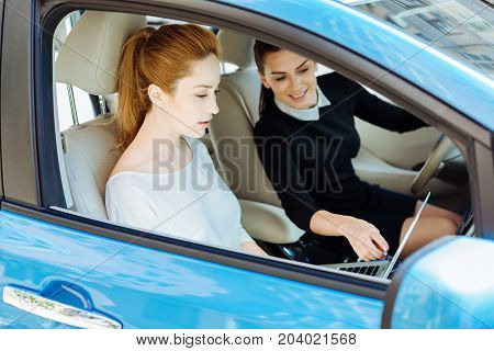 Look at this. Attractive delighted cheerful woman smiling and pointing at the laptop screen while sitting behind the wheel
