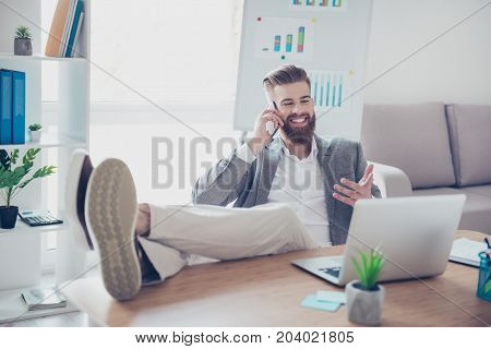 Handsome young guy in formalwear talking on mobile phone and telling about his achievement sitting at the office with feet on the desk top gesturing