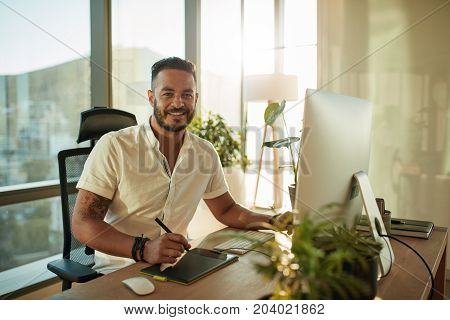Portrait of creative young man working in office with graphic tablet. Handsome male designer working at his desk and smiling.