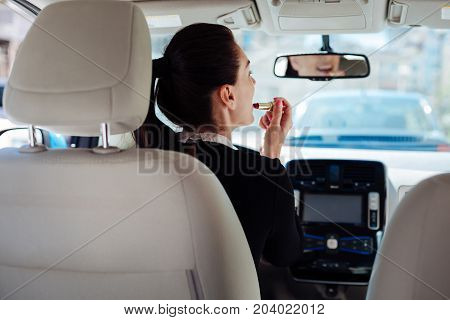 Always beautiful. Attractive nice beautiful woman looking into the rear view mirror and holding a lipstick while putting it on