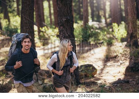 Man and woman hikers trekking in forest. Hiker couple exploring nature walking through the woods.