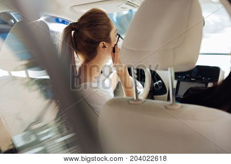 Being beautiful. Nice attractive pleasant woman sitting in the car and putting on makeup while preparing for work