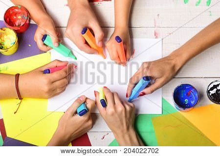 Markers In Male And Female Hands Draw On Blank Paper