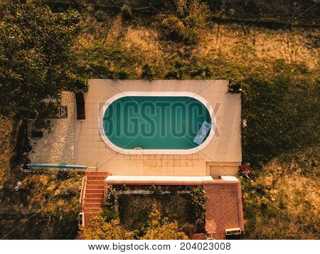 Aerial view of house backyard with swimming pool in summer sunset top view of private poolside from drone pov