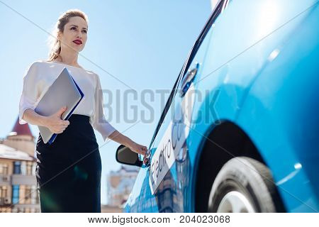Ready to leave. Attractive nice confident businesswoman holding her documents and opening the car while being ready to leave