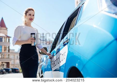 Hot tea. Attractive pleasant nice businesswoman holding a thermos bottle and smiling while standing near her car